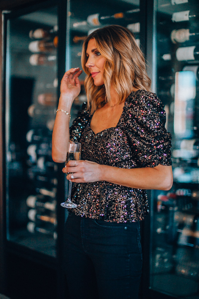 fashion blogger cella jane wearing black sequin holiday party top with black skinny jeans paired with nude heels